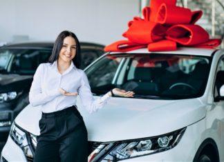 nő fehér autóval hatalmas piros masnival
