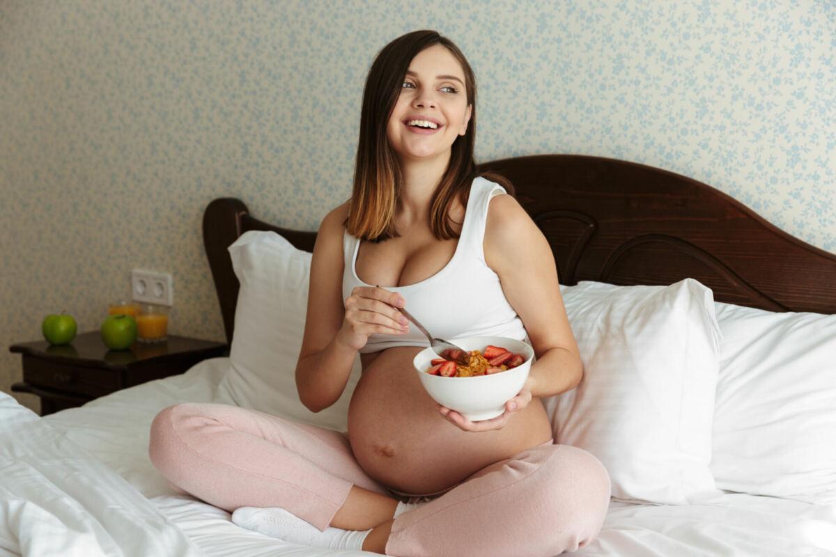 terhes nő ágyon ülve müzlit eszik